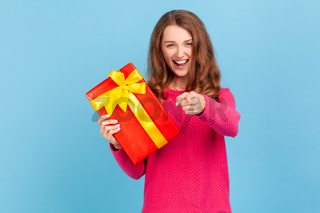 Woman holding present box and pointing finger to camera with excited expression.