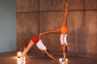 Two young slender women in colorful sportive wears doing yoga for relax, attractive females performing stretching exercise