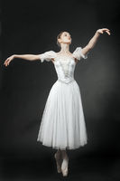Beautiful dancer posing in a white dress, on studi