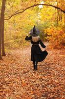Unrecognizable witch walking in autumn forest
