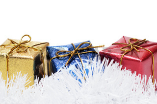 colorful present boxes on tinsel over white background