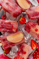 Strawberry raspberry apple and red currant ice cream popsicles in metal tray with ice cubes