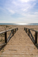 A wooden boardwalk and beach access leads directly onto beach with glistening calm ocean behind