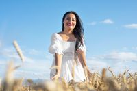 Young Woman in white dress standing on golden wheat field at sunny day, touching gently the wheat.