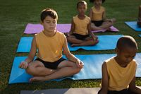 Caucasian boy practicing yoga and meditating sitting on yoga mat in garden at school
