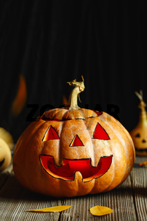 Halloween design with pumpkins. Horrible symbol of Halloween - Jack-o-lantern. Scary head of pumpkin with flame and a few small painted gourds. Glowing face, trick or treat. Copy Space