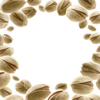 Salted pistachios levitate on a white background