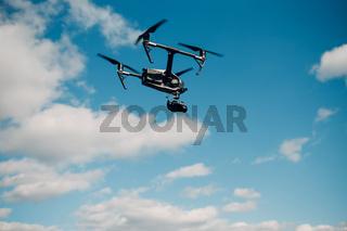 Big quadcopter drone against blue sky aerial flight and filming.