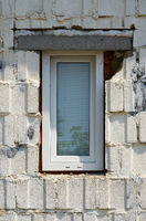 Unprofessionally installed window in the facade of a house with construction defects