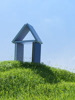 House made of books on a small grassy hill