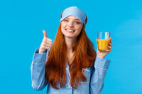 Drinking fresh juice is healthy and good. Cute glamour redhead caucasian female in sleep mask and nightwear, tilt head and smiling holding drink in glass and show thumb-up smiling