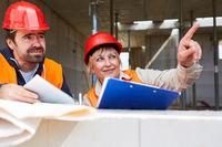 Architektin auf Baustelle gibt Arbeiter eine Anweisung