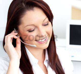 Glowing young businesswoman wearing headphones smiling at the camera