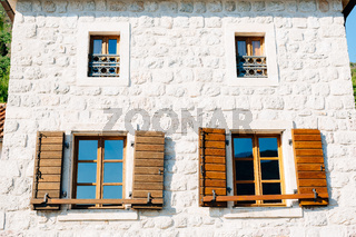 The house is white brick with large windows and wooden shutters below and small windows with metal bars above them.