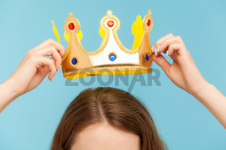 woman putting on head golden crown, concept of awards ceremony, privileged status
