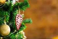 Composition of christmas tree with gold baubles and decorations on blurred background