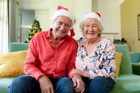 Happy caucasian senior couple in santa hats having video call at christmas time