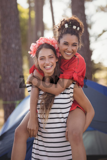 Portrait of cheerful woman piggybacking her female friend