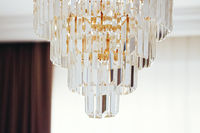 Crystal glass chandelier with golden details, luxury furniture and home decor concept