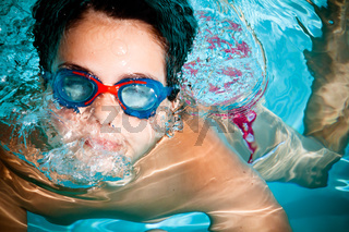 A kid swimming and having a good time in a pool. Sports concept.