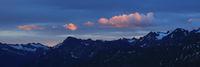 Sunrise scene in the Bernese Oberland. Bright lit cloud over dark mountains.