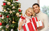 happy couple with christmas gifts at home