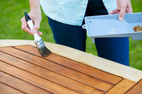 woman painting wooden exotic wood table in the garden with a brush