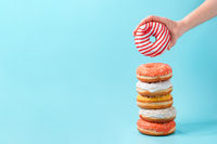 Stack of donuts, donut in hand on blue, copy space