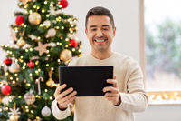 happy middle aged man with tablet pc on christmas
