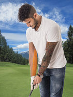 Man playing golf in green field