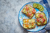 Plate with toasts with cucomber, tomatoes and crumbled feta and radish sprouts