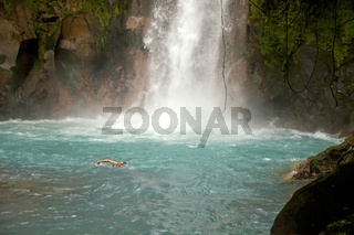 Tourist schwimmt am Wasserfall mit blauem Wasser des Rio Celeste im Mationalpark Volcán Tenorio