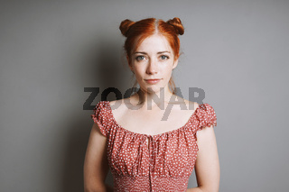 indoor portrait of smiling young woman with red hair space buns