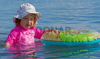 Kleinkind spielt mit Schwimmring im Wasser