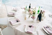 Wedding dinner table reception. White square plates on a round table with pink rag napkins with a black heart. White chairs Chiavari, Tiffany.