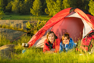 Young camping couple lying in tent