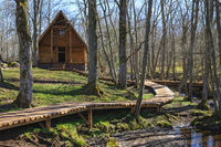 Log house at a glade in a woodland and a wood footpath