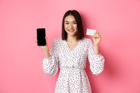 Cute asian woman shopping online, showing bank credit card and mobile screen, smiling and looking at camera, standing over pink background