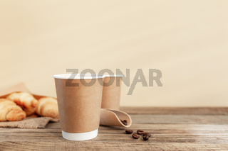 Two paper cups of coffee, croissants, coffee beans and spoon at wooden table