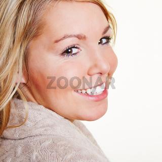 Blonde Frau schaut über die Schulter