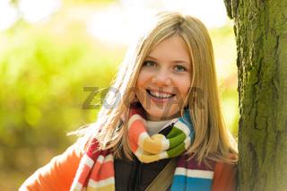 Smiling teenager blonde girl woods tree autumn