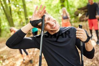 Schwitzender Fitness Trainer beim Nordic Walking