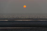 Orange sun setting over the sea seen from the beach