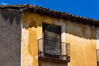 Old Iron Balcony in Aged Yellow Plaster Facade