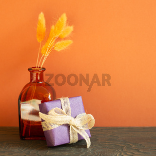 Purple gift box and dry flowers on wooden table. red wall background