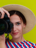 Portrait of beautiful female photographer shooting close up