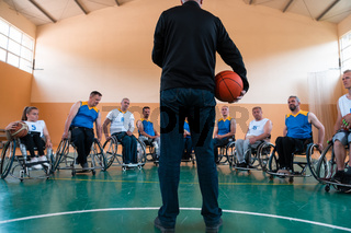 selector I explain new tactics to basketball players in wheelchairs, players sit in wheelchairs listening to the selector
