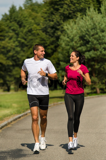 Caucasian couple running in park