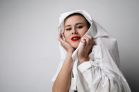 Close-up portrait of bald pretty woman with red lips, posing on white wall.