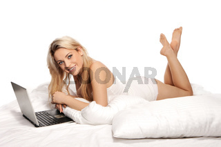 Beautiful blonde using a laptop on a bed